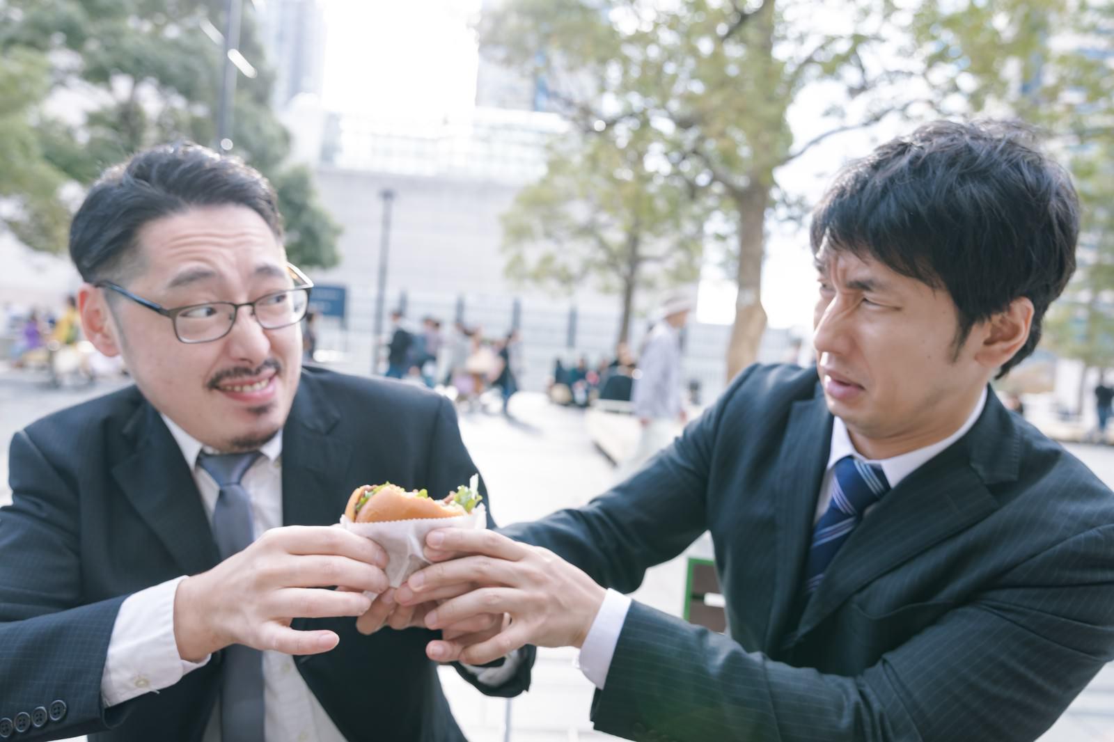 「絶品ハンバーガーを奪い合う上司と部下」の写真[モデル:大川竜弥 ゆうせい]