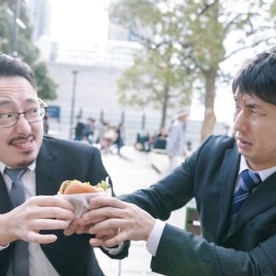 絶品ハンバーガーを奪い合う上司と部下の写真