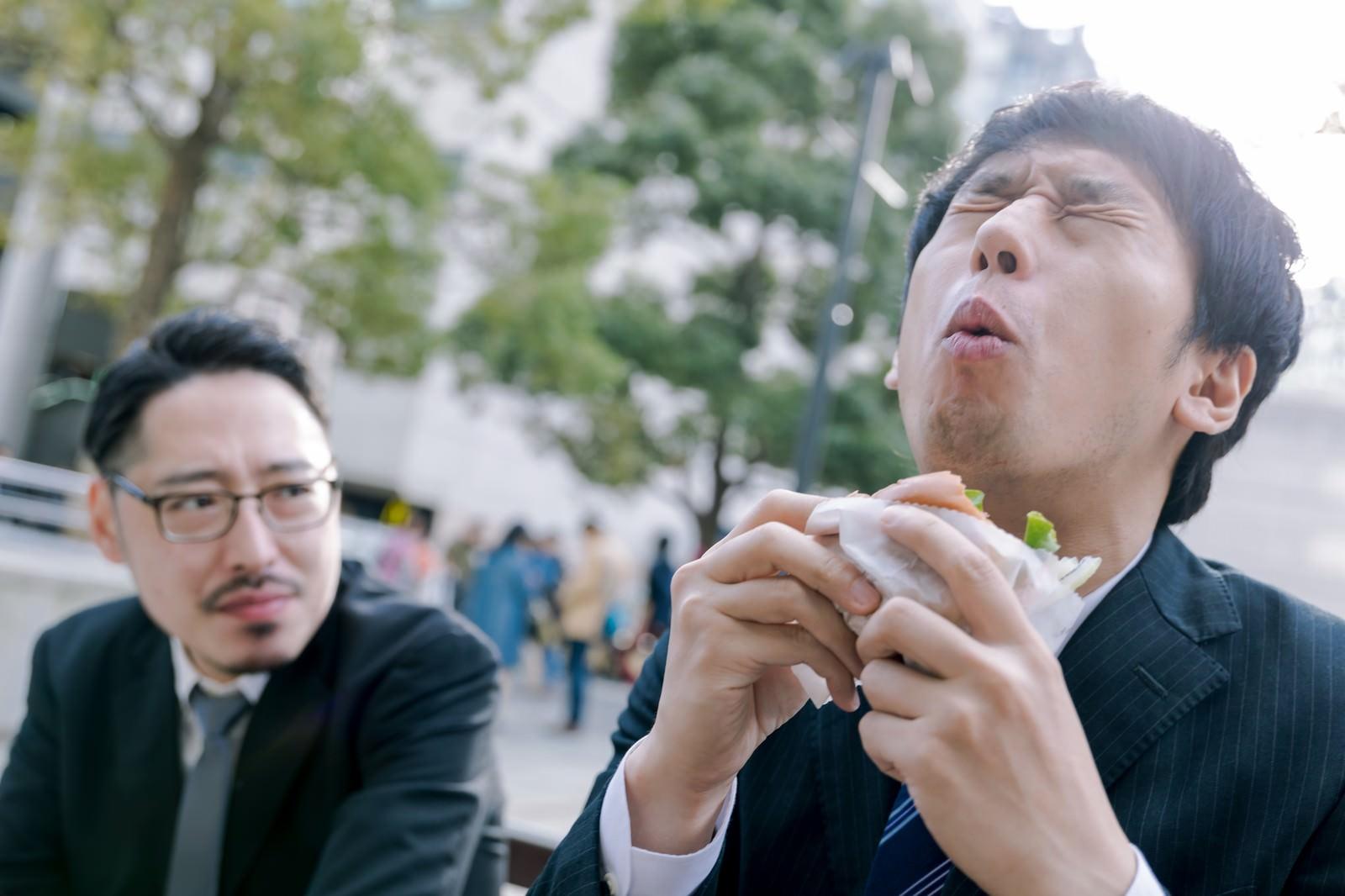 「カメラが回っている時だけオーバーリアクション気味にグルメレビューする男性と横目のプロデューサー」の写真[モデル:ゆうせい 大川竜弥]