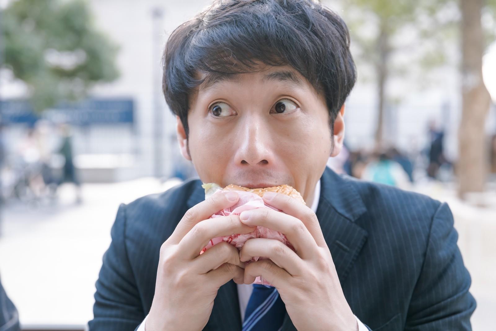 「一心不乱にハンバーガーにかぶりつく会社員」の写真[モデル:大川竜弥]