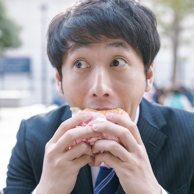 一心不乱にハンバーガーにかぶりつく会社員の写真