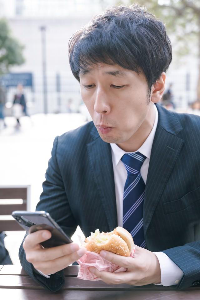 忙しなくランチにハンバーガーを食べる男性会社員の写真
