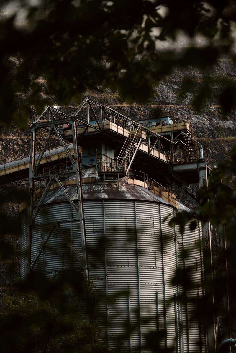 「茂みの向こうに見える古い工場(採石場)」の写真
