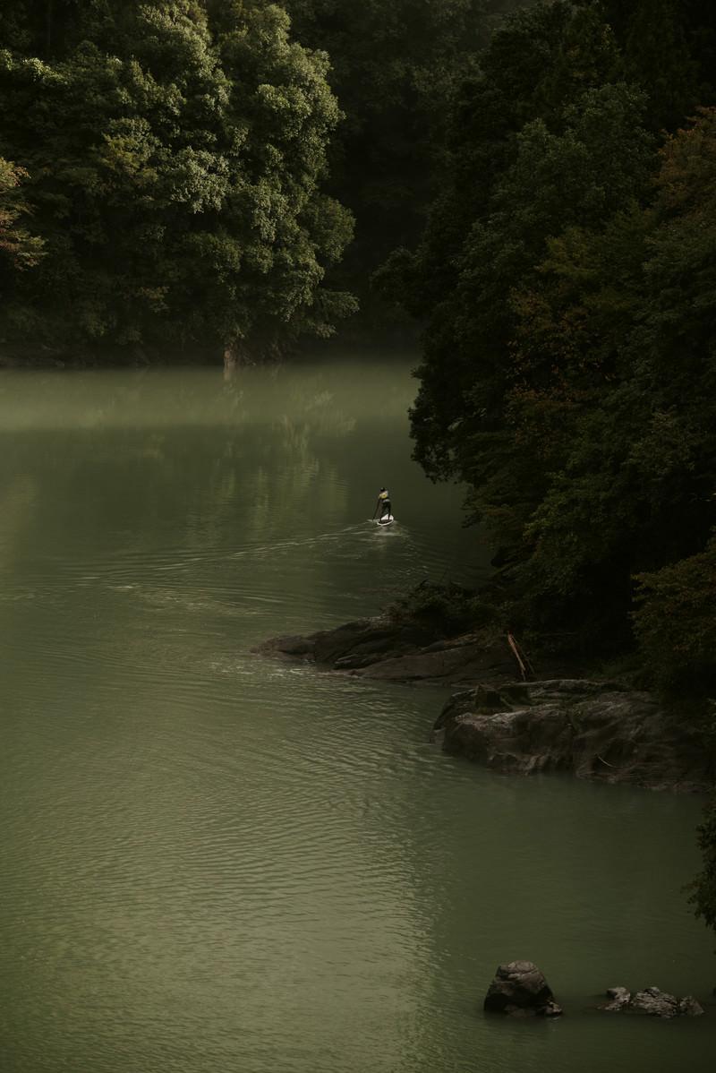 「山中の川でパドルボートを楽しむ男(奥多摩)」の写真