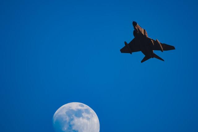 夕日を浴びるF-4と輝きを増す月の写真