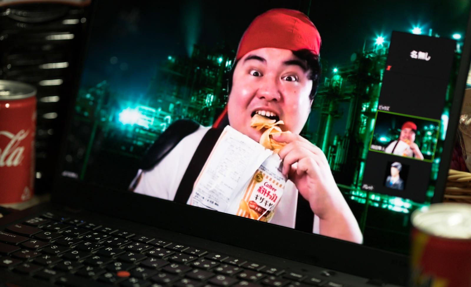 「ポテチ食べながらビデオ通話する男性」の写真[モデル:段田隼人]