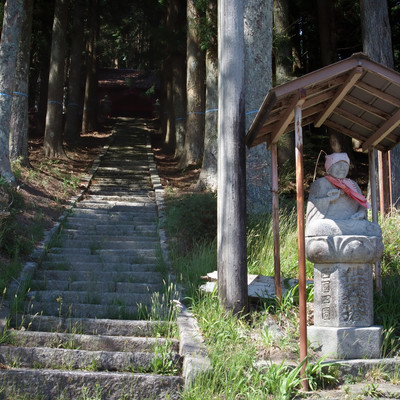 山のお社に続く階段と入り口の石仏の写真