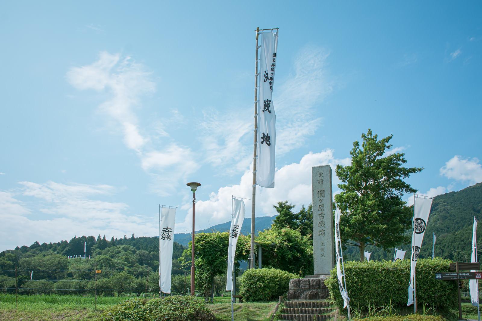 「関ケ原決戦地の石碑とその左奥に見える石田三成陣跡の展望デッキの旗印とノボリ」の写真